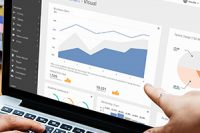 Hands gesturing at laptop screen with data analytics graphs